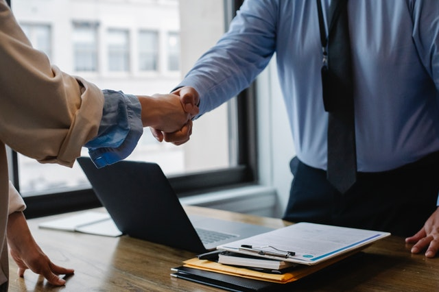An employer shaking hands with a newly hired employee who learnt the skills for the interview from a corporate career coaching company.