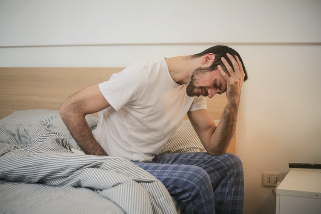 A man with urge incontinence sitting on a bed with his hand on his head.