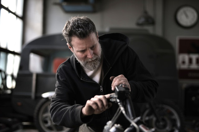 A man taking apart a car to sell used auto parts online.